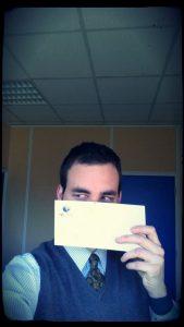 Un homme tient une enveloppe devant son visage